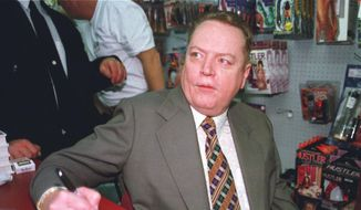 """Hustler"" Magazine publisher Larry Flynt signs a copy of ""The People Vs. Larry Flynt"" in his downtown Cincinnati ""Hustler"" store on April 30, 1998. Flynt, who turned ""Hustler"" magazine into an adult entertainment empire while championing First Amendment rights, has died at age 78. His nephew, Jimmy Flynt Jr., told The Associated Press that Flynt died Wednesday, Feb. 10, 2021, of heart failure at his Hollywood Hills home in Los Angeles. (AP Photo/Tom Uhlman, File)"
