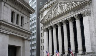 FILE - This Monday, Nov. 23, 2020 file photo shows the New York Stock Exchange, right, in New York.  Small stocks are delivering the biggest punch on Wall Street. Over the last three months, an index that tracks 2,000 of the smallest stocks in the U.S. market has more than tripled the gains of the big-cap S&P 500.  (AP Photo/Seth Wenig, File)