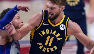 Indiana Pacers forward Domantas Sabonis (11) runs into the defense of Detroit Pistons forward Blake Griffin during the first half of an NBA basketball game, Thursday, Feb. 11, 2021, in Detroit. (AP Photo/Carlos Osorio)