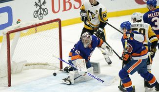 Pittsburgh Penguins center Sidney Crosby (87) and New York Islanders goaltender Semyon Varlamov (40) watch as a shot by Penguins center Evgeni Malkin (71) approaches the goal line near the end of the third period of an NHL hockey game Thursday, Feb. 11, 2021, in Uniondale, N.Y. The shot tied the game, which the Penguins won 4-3 in a shootout. (AP Photo/Kathy Willens)