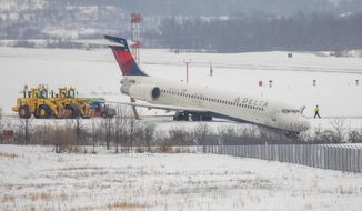 """A Delta airplane stuck in a large ditch at Pittsburgh International Airport on Thursday, Feb. 11, 2021 in Moon Township. The Boeing 717 was departing for Atlanta with 77 people on board when it """"exited a taxiway"""" just prior to takeoff near a runway. (Andrew Rush/Pittsburgh Post-Gazette via AP)"""