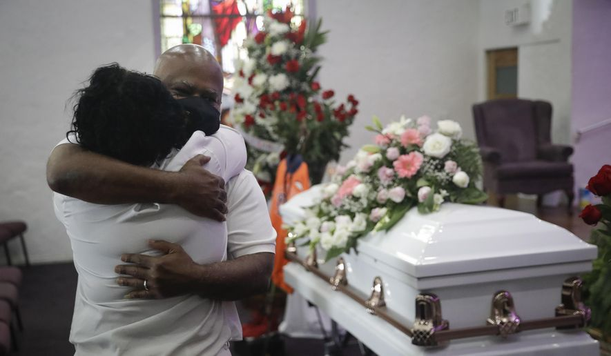 In this July 21, 2020, photo, Darryl Hutchinson, facing camera, is hugged by a relative during a funeral service for Lydia Nunez, who was Hutchinson's cousin at the Metropolitan Baptist Church in Los Angeles. Nunez died from COVID-19. California has edged past New York in the grim statistic of the number of deaths due to COVID-19, according Johns Hopkins University data reported Thursday, Feb. 11, 2021. (AP Photo/Marcio Jose Sanchez) **FILE**