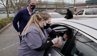 Gov. Gavin Newsom watches as LVN Cari Elkins gives a COVID-19 vaccination at a drive-thru vaccination center at Natomas High School in Sacramento, Calif., Thursday, Feb. 11, 2021. Appointments were needed for the 1,000 vaccinations to be administered for those 65 and over, first responders, health workers, teachers, food and agricultural employers. Called an equitable distribution site, it prioritized those disproportionally impacted by COVID-19, was collaboration between the Natomas' Unified School District, Sacramento County Public Health Department and Sacramento Vice Mayor Angelique Ashby who represents the area. (AP Photo/Rich Pedroncelli)