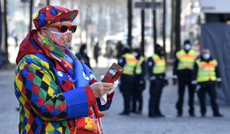 """A carnival reveler is watched by public order guards at the """"Alter Markt"""" where normally tens of thousands of revelers dressed in carnival costumes would celebrate the start of the street carnival in Cologne, Germany, Thursday, Feb. 11, 2021. This year all carnival celebrations are banned due to the coronavirus pandemic. (AP Photo/Martin Meissner)"""