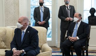 Gov. Larry Hogan, R-Md., left, and Mayor Mike Duggan, D-Detroit, listen as President Joe Biden speaks during a meeting with a bipartisan group of mayors and governors to discuss a coronavirus relief package, in the Oval Office of the White House, Friday, Feb. 12, 2021, in Washington. (AP Photo/Evan Vucci)