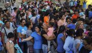 """Migrants, many of whom were returned to Mexico under the Trump administration's """"Remain in Mexico"""" policy, wait in line to get a meal in an encampment near the Gateway International Bridge in Matamoros, Mexico, Aug. 30, 2019. The Biden administration on Friday, Feb. 12, 2021, announced plans for tens of thousands of asylum-seekers waiting in Mexico for their next immigration court hearings to be released in the United States while their cases proceed. (AP Photo/Veronica G. Cardenas, File)  **FILE**"""