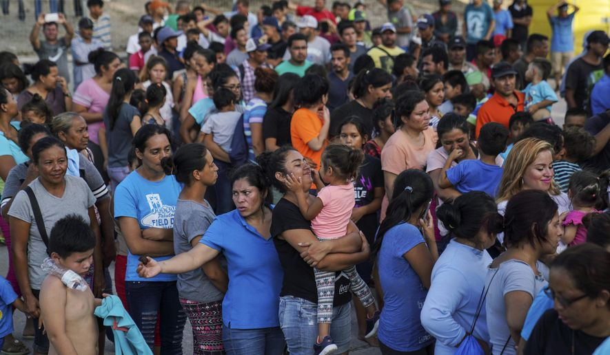 "In this Aug. 30, 2019, file photo, migrants, many of whom were returned to Mexico under the Trump administration's ""Remain in Mexico"" policy, wait in line to get a meal in an encampment near the Gateway International Bridge in Matamoros, Mexico. The Biden administration on Friday, Feb. 12, 2021, announced plans for tens of thousands of asylum-seekers waiting in Mexico for their next immigration court hearings to be released in the United States while their cases proceed. (AP Photo/Veronica G. Cardenas, File)  **FILE**"