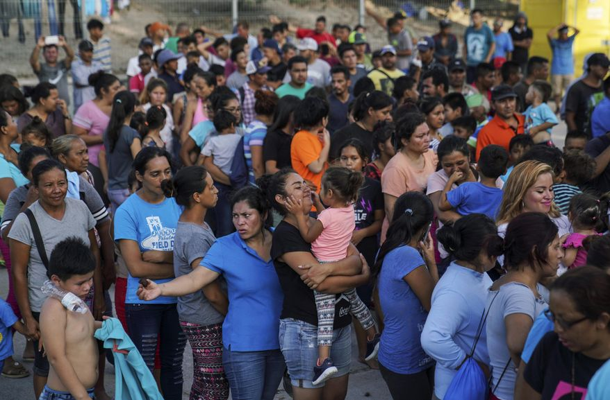 "Migrants, many of whom were returned to Mexico under the Trump administration's ""Remain in Mexico"" policy, wait in line to get a meal in an encampment near the Gateway International Bridge in Matamoros, Mexico, Aug. 30, 2019. The Biden administration on Friday, Feb. 12, 2021, announced plans for tens of thousands of asylum-seekers waiting in Mexico for their next immigration court hearings to be released in the United States while their cases proceed. (AP Photo/Veronica G. Cardenas, File)  **FILE**"