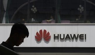 FILE - In this Thursday, May 16, 2019 file photo, a man is silhouetted near the Huawei logo in Beijing. Huawei took U.K. bank HSBC to court on Friday, Feb. 12, 2021 seeking documents the Chinese company says are key to its legal efforts to stop its chief financial officer from being extradited to the U.S. from Canada. (AP Photo/Ng Han Guan, file)