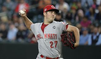 FILE - In this Sept. 10, 2019, file photo, Cincinnati Reds starting pitcher Trevor Bauer throws to a Seattle Mariners batter during the first inning of a baseball game in Seattle. Trevor Bauer is coming home to pitch for the World Series champion Los Angeles Dodgers. The reigning NL Cy Young Award winner was introduced Thursday, Feb. 11, 2021 on the field at Dodger Stadium. (AP Photo/Ted S. Warren, File)