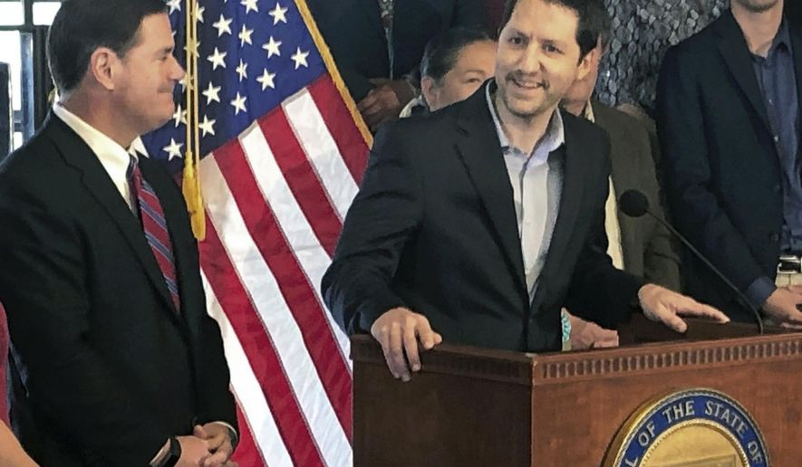 FILE - In this May 28, 2019 file photo Arizona Republican Sen. Paul Boyer, at the podium, is seen with Arizona Gov. Doug Ducey during a news conference in Phoenix. For months, four elected Republicans and one Democrat on the board overseeing Arizona's most populous county have been facing threats and harassment for backing election results that saw Democrat Joe Biden win the state. That fury from some backers of President Donald Trump moved on this week to Boyer a Republican state senator, who had to change his phone number, move his wife and young son and get police protection after he voted against a measure to subject the supervisors to arrest for refusing to hand election materials over to the Senate. (AP Photo/Jonathan J. Cooper, File)