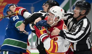 Vancouver Canucks center Jay Beagle (83) tussles with Calgary Flames left wing Matthew Tkachuk (19) during the second period of an NHL hockey game Thursday, Feb. 11, 2021, in Vancouver, British Columbia. (Jonathan Hayward/The Canadian Press via AP)
