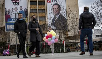 """Pedestrians walk past a man selling balloons in front of electoral poster with portrait of the candidate for the prime minister of """"Self-Determination"""" party Albin Kurti, right, and candidate for president of Alliance for Future of Kosovo """"AAK"""" Ramush Haradinaj in capital Pristina, Kosovo, on Wednesday, Feb. 10, 2021. Kosovo holds an early general election on upcoming Sunday Feb. 14, amid the coronavirus pandemic, economic downturn and stalled negotiations with wartime foe Serbia.(AP Photo/Visar Kryeziu)"""