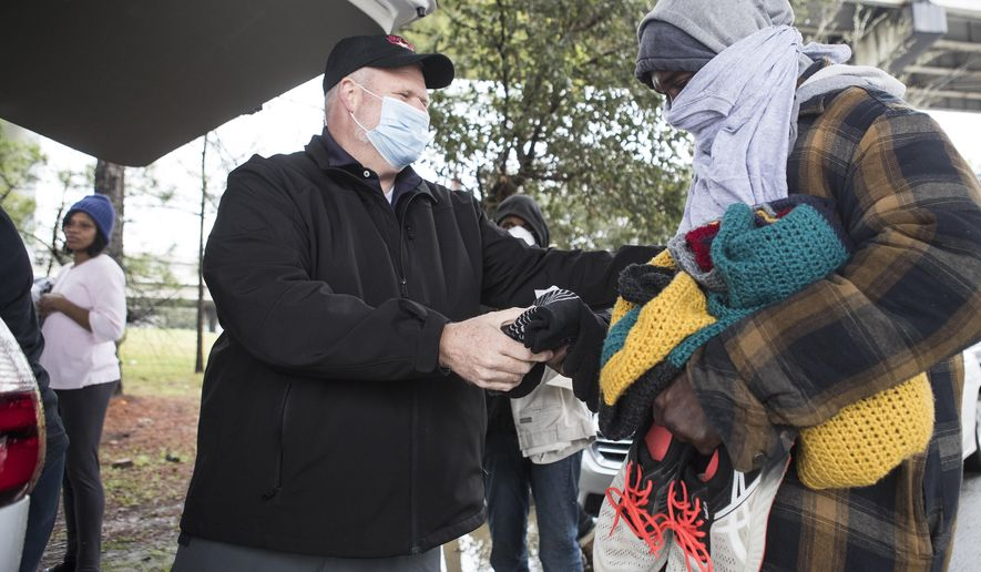 Ray Walker, left, of the Star of Hope, hands out blankets and cold-weather essentials to Larry Promise Friday, Feb. 12, 2021, in Houston. The Star of Hope Love In Action van makes periodic trips out into the city's street homeless population to give out blankets, coats, and other cold-weather essentials during frigid weather.  (Brett Coomer/Houston Chronicle via AP)