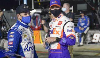 Ricky Stenhouse Jr., left, and Denny Hamlin talks on pit road before the first of two qualifying NASCAR auto races for the Daytona 500 at Daytona International Speedway, Thursday, Feb. 11, 2021, in Daytona Beach, Fla. (AP Photo/John Raoux)