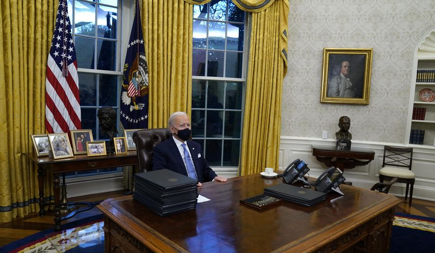 In this Wednesday, Jan. 20, 2021, file photo, President Joe Biden pauses as he signs his first executive orders in the Oval Office of the White House in Washington.On Friday, Feb. 12, 2021, The Associated Press reported on a manipulated photo circulating online incorrectly asserting it shows Biden asleep in his seat at the Resolute Desk in the Oval Office with a stack of executive orders in front of him. Biden's head in the post comes from a 2011 event where he appears to briefly doze off as former President Barack Obama delivered a speech on the national debt. (AP Photo/Evan Vucci)