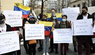 "People protest against the extradition of Venezuelan Ernesto Quintero in Madrid, Spain, Friday, Feb. 12, 2021. The extradition of 40-year-old Ernesto Quintero triggered protests Friday among the Venezuelan community in Spain and opposition groups of the Venezuela government of Nicolas Maduro. Spain's National Court has approved the extradition of a financial broker wanted in Venezuela on charges of fraud and embezzlement of funds. Banners reads in Spanish: ""In Venezuela human rights are violated"", ""No to the extradition of an innocent"". (Oscar Canas/Europa Press via AP)"