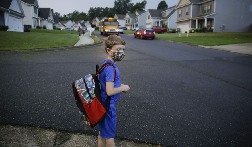 In this Aug. 3, 2020, file photo, Paul Adamus, 7, waits at the bus stop for the first day of school in Dallas, Ga. Amid mounting tensions about school reopening, the Centers for Disease Control and Prevention planned to release long-awaited guidance Friday, Feb. 12, 2021, on what measures are needed to get children back into the classroom during the pandemic. (AP Photo/Brynn Anderson, File)
