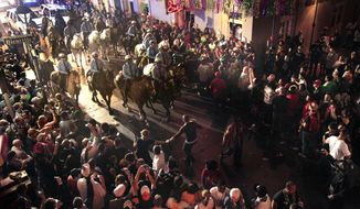 File - In this March 9, 2011 file photo, police on horseback and foot clear out the crowds on Bourbon Street at midnight for the end of Mardi Gras festivities in New Orleans. The final weekend of Mardi Gras season in New Orleans has begun with a warning from police that crowds won't be tolerated as the city fights to stop the spread of the coronavirus. Police chief Shaun Ferguson noted Friday, Feb. 12, 2021, that bars throughout the city were being ordered to close through Fat Tuesday. And he said police will man barricades limiting pedestrian traffic on Bourbon Street to people who live or work there, hotel guests, and restaurant patrons. T (AP Photo/Gerald Herbert, File)