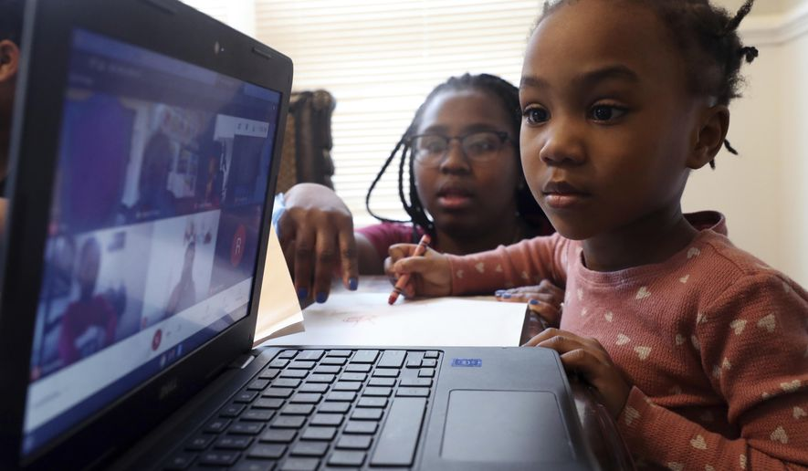 FILE - In this Feb. 10, 2021, file photo, Lear Preston, 4, who attends Scott Joplin Elementary School, participates in her virtual classes as her mother, Brittany Preston, background, assists at their residence in Chicago's South Side. Amid mounting tensions about reopening schools, the Centers for Disease Control and Prevention planned to release long-awaited guidance Friday, Feb. 12, on what measures are needed to get children back into the classroom during the pandemic. (AP Photo/Shafkat Anowar, File)