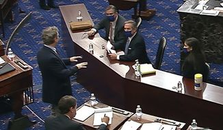 In this image from video, Sen. Rand Paul, R-Ky.,, standing last left, talks with Bruce Castor and Michael van der Veen, attorney's for former President Donald Trump, as the Senate votes on a motion to call witnesses during the second impeachment trial of former President Donald Trump in the Senate at the U.S. Capitol in Washington, Saturday, Feb. 13, 2021. (Senate Television via AP)