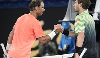 Spain's Rafael Nadal, left, shakes hands with Britain's Cameron Norrie after winning their third round match a the Australian Open tennis championships in Melbourne, Australia, Saturday, Feb. 13, 2021. (AP Photo/Andy Brownbill)