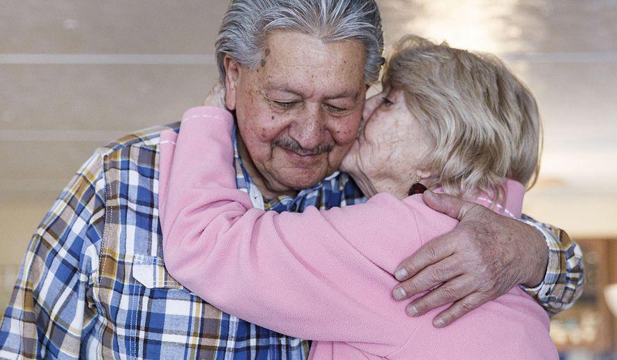 Leatha Houghtaling, 85, kisses John DiMeglio, 81, on the cheek in Cody, Wyo., on Feb. 9, 2021. The two met at the Cody Senior Center. (Lauren Modler/The Cody Enterprise via AP)