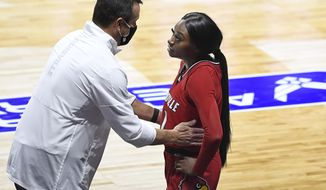 """FILE - In this Dec. 4, 2020, file photo, Louisville head coach Jeff Walz, left, speaks with Louisville's Dana Evans during the second half of an NCAA college basketball game against DePaul in Uncasville, Conn. Louisville coach Jeff Walz first heard his 5-year-old daughter sing the national anthem while she was in the playroom this week. He was blown away. So was his team after it heard a recorded rendition of Lucy singing """"The Star-Spangled Banner"""" on Thursday night before the Senior Night game against Georgia Tech. (AP Photo/Jessica Hill, File)"""