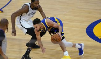 Golden State Warriors guard Stephen Curry, right, is defended by Brooklyn Nets forward Kevin Durant during the first half of an NBA basketball game in San Francisco, Saturday, Feb. 13, 2021. (AP Photo/Jeff Chiu)