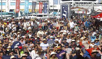 Spectators watch on again screen Italy's Luna Rossa race Britain's INEOS Team UK in the Prada Cup on Auckland's Waitemata Harbour, New Zealand, Saturday, Feb. 13, 2021. (Brett Phibbs/NZ Herald via AP)