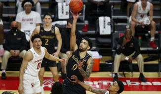 Northwestern's Boo Buie (0) shoots over Rutgers defenders during the first half of an NCAA college basketball game in Piscataway, N.J., Saturday, Feb. 13, 2021. (AP Photo/Noah K. Murray)