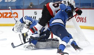 Winnipeg Jets goaltender Connor Hellebuyck (37) saves the puck as Tucker Poolman (3) defends against Ottawa Senators' Colin White (36) during the first period of an NHL hockey game in Winnipeg, Manitoba, Saturday, Feb. 13, 2021. (John Woods/The Canadian Press via AP)