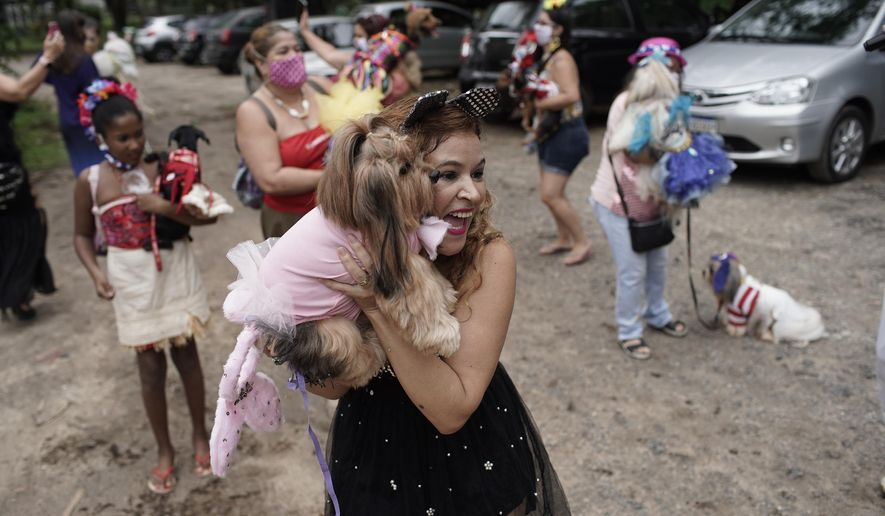 Francisca poses with her pet dog Eva during the annual dog Carnival parade in Rio de Janeiro, Brazil, Saturday, Feb. 13, 2021. Rio's Carnival festivities were canceled due to the new coronavirus pandemic, but pet lovers from around the city gathered for the Carnival tradition that drew participants with their furry, four-legged companions to compete for best costume. (AP Photo/Silvia Izquierdo)