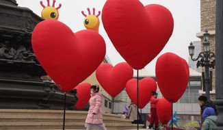 Visitors wearing a mask to protect from the coronavirus stand near heart shaped balloons displayed at a mall district during the second day of the Chinese Lunar New Year in Beijing on Saturday, Feb. 13, 2021. (AP Photo/Ng Han Guan)