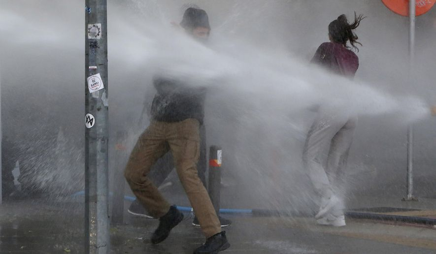 Police spray protestors with a water canon, during a protest against the alleged corruption with the Mediterranean island nation's governing elites in capital Nicosia, Cyprus, Saturday, Feb. 13, 2021. Police said that at least eight demonstrators were taken into custody. Police dispersed the demonstration in line with a government order against public gatherings because of ongoing restrictions to prevent a possible flare-up of COVID-19 infections. (AP Photo/Petros Karadjias)