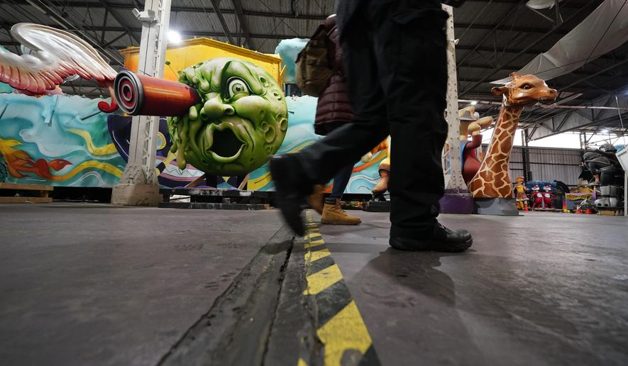 People walk past parts of Mardi Gras floats past and present, at Mardi Gras World, where Kern Studios creates and stores some of their floats, in New Orleans, Friday, Feb. 12, 2021. New Orleans' annual pre-Lenten Mardi Gras celebration is muted this year because of the coronavirus pandemic. Parades canceled. Bars closed. Crowds suppressed. Mardi Gras joy is muted this year in New Orleans as authorities seek to stifle the coronavirus's spread. And it's a blow to the tradition-bound city's party-loving soul. (AP Photo/Gerald Herbert)