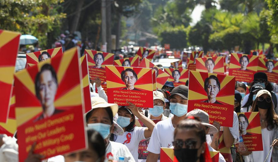 Protesters hold posters with an image of deposed leader Aung San Suu Kyi in Yangon, Myanmar, on Sunday. Vast numbers of people have flouted orders against demonstrations to march against the military takeover. (ASSOCIATED PRESS)