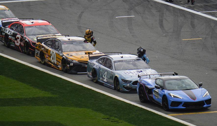 Drivers wait by their cars during a weather delay in the NASCAR Daytona 500 auto race at Daytona International Speedway, Sunday, Feb. 14, 2021, in Daytona Beach, Fla. (AP Photo/Chris O'Meara)