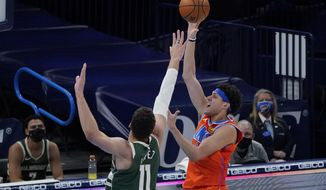 Oklahoma City Thunder forward Justin Jackson, right, shoots in front of Milwaukee Bucks center Brook Lopez (11) in the first half of an NBA basketball game Sunday, Feb. 14, 2021, in Oklahoma City. (AP Photo/Sue Ogrocki)