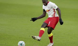 Leipzig's Dayot Upamecano plays the ball during the German Bundesliga soccer match between RB Leipzig and 1. FC Cologne in Leipzig, Germany, Saturday, Dec. 19, 2020. (AP Photo/Michael Sohn)