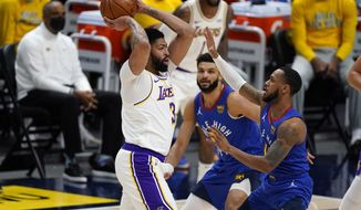 Los Angeles Lakers forward Anthony Davis, left, looks to pass the ball as Denver Nuggets guards Jamal Murray, center, and Monte Morris defend during the first half of an NBA basketball game Sunday, Feb. 14, 2021, in Denver. (AP Photo/David Zalubowski)