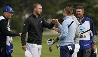 Daniel Berger, second from left, is greeted by playing partners Patrick Cantlay, second from right, and Russell Knox, third from right, on the 18th green of the Pebble Beach Golf Links after finishing the final round of the AT&T Pebble Beach Pro-Am golf tournament Sunday, Feb. 14, 2021, in Pebble Beach, Calif. Berger won the tournament. (AP Photo/Eric Risberg)