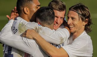 Real Madrid celebrate after scoring their second goal during the Spanish La Liga soccer match between Real Madrid and Valencia at the Alfredo Di Stefano stadium in Madrid, Spain, Sunday, Feb. 14, 2021. (AP Photo/Manu Fernandez)