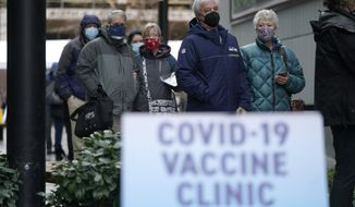 In this Jan. 24, 2021, file photo, people stand near a sign as they wait in line to receive the first of two doses of the Pfizer vaccine for COVID-19 at a one-day vaccination clinic set up in an Amazon.com facility in Seattle and operated by Virginia Mason Franciscan Health. Scientists say it's still too early to predict the future of the coronavirus, but many doubt it will ever go away entirely. (AP Photo/Ted S. Warren, File)