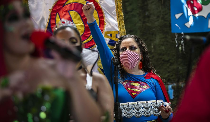 """A woman dressed as a superhero and wearing a mask to curb the spread of the new coronavirus performs in the """"Desliga da Justica"""" street band in Rio de Janeiro, Brazil, Sunday, Feb. 14, 2021. Their performance was broadcast live on social media for those who were unable to participate in the carnival due to COVID restrictions after the city's government officially suspended Carnival and banned street parades or clandestine parties. (AP Photo/Bruna Prado)"""