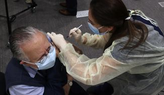 A healthcare worker receives Pfizer-BioNTech COVID-19 vaccine during a nationwide vaccination program at the American University Medical Center in Beirut, Lebanon, Sunday, Feb. 14, 2021. (AP Photo/Bilal Hussein)