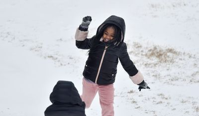 Shamiya Evans, 9, throws a handful of snow at Kynlee Kelly, 8, in Ridgeland, Mississippi.