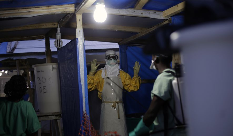 In this Nov. 20, 2014 file photo, an MSF Ebola heath worker is sprayed as he leaves the contaminated zone at the Ebola treatment centre in Gueckedou, Guinea. Guinea has officially declared an Ebola epidemic Monday Feb. 15, 2021, after at least three people have died and others have been infected in the West African nation. (AP Photo/Jerome Delay-File)  **FILE**