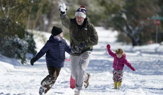 Craig Crow, center, throws snowballs as he plays in the snow with his children and neighbors, Monday, Feb. 15, 2021, in San Antonio. San Antonio received 3-5 inches of snow over night. (AP Photo/Eric Gay)