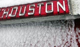 A sign is covered in ice and snow Monday, Feb. 15, 2021, in Houston. A winter storm dropping snow and ice sent temperatures plunging across the southern Plains, prompting a power emergency in Texas a day after conditions canceled flights and impacted traffic across large swaths of the U.S. (AP Photo/David J. Phillip)